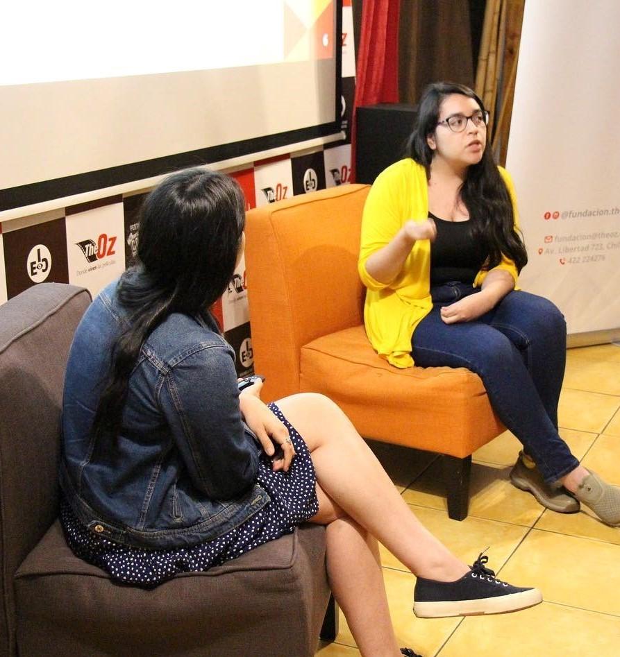 La terapeuta está sentada sola en un sillón moviendo su mano, frente a ella está la otra expositora sentada en otro sillón. Ambas miran hacia el público.