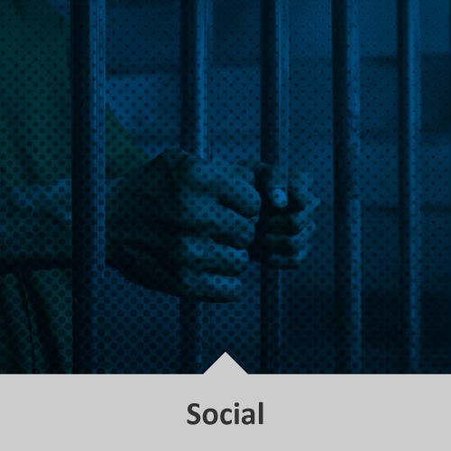 Manos de persona privada de libertad, tomando la reja de la celda, en tonos azules oscuros. Temática: Social